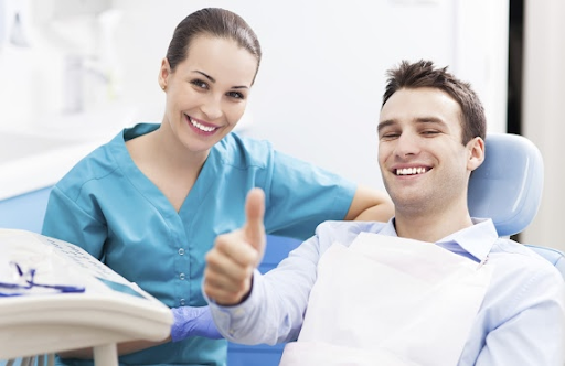 young man gives thumbs up at dentist